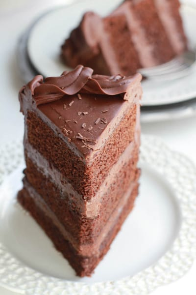 Ultimate Triple Chocolate Layer Cake - The best triple layer chocolate cake with the easiest milk chocolate frosting covered with mini chocolate chips.